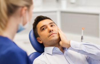 A dentist consulting a male patient with TMJ.