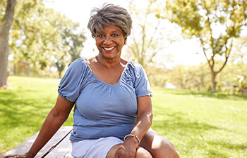 Smiling mature Afro-American woman in the park.
