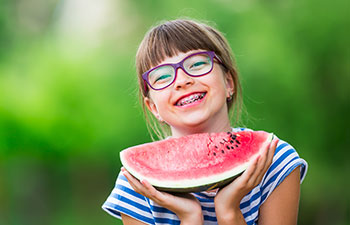 Girl with braces holds a watermelon.