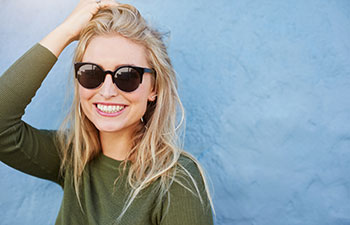 Happy, smilling blonde woman wearing sunglasses.