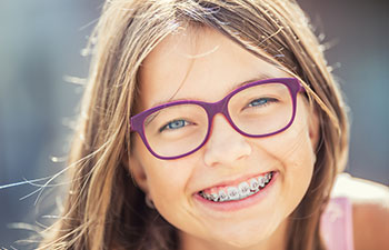 Smiling girl with glasses wearing dental braces.