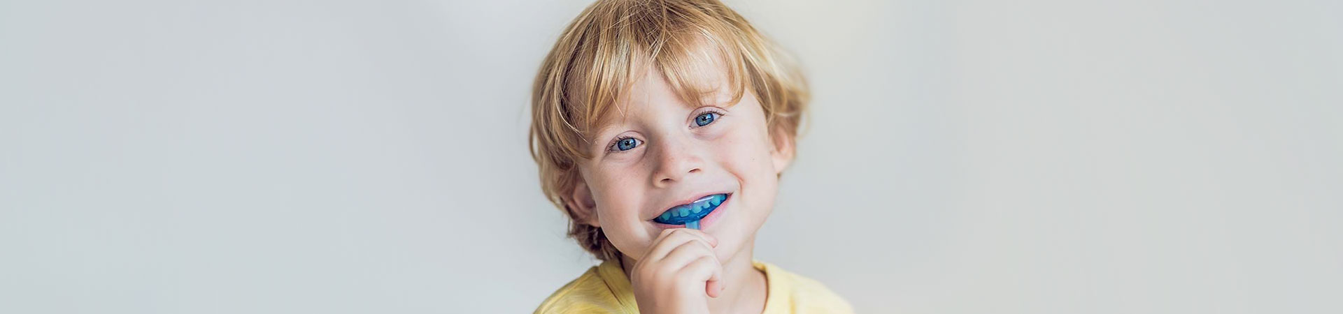 Boy with nightguard in his mouth.