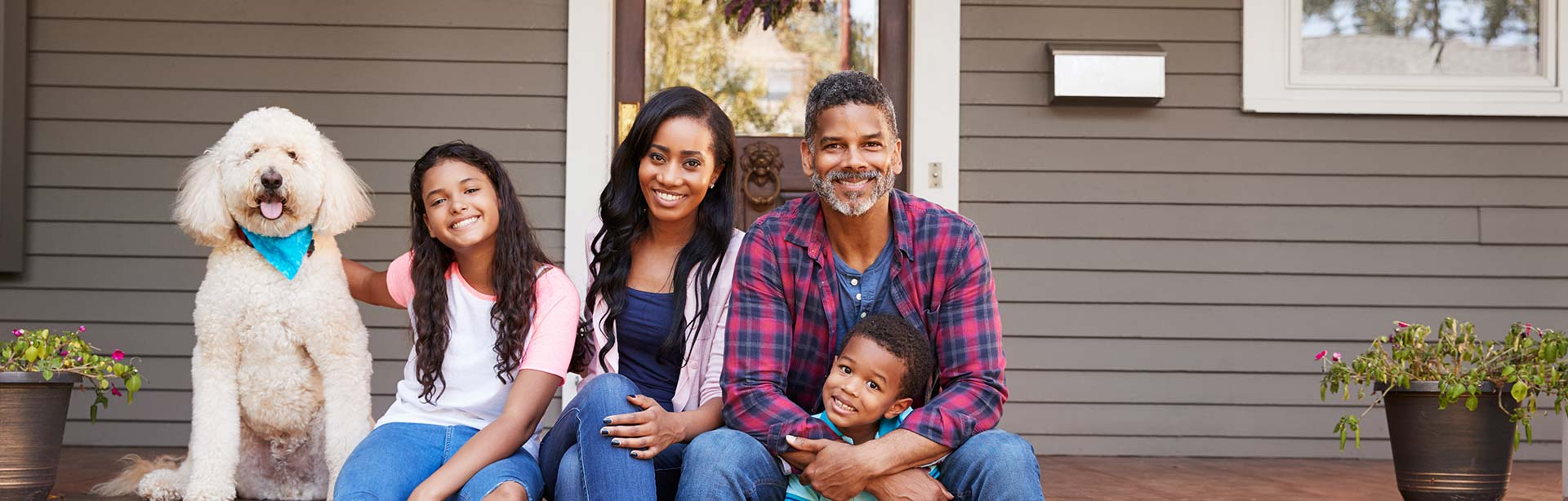Happy Afro-American family of four with their dog sitting on the porch steps.