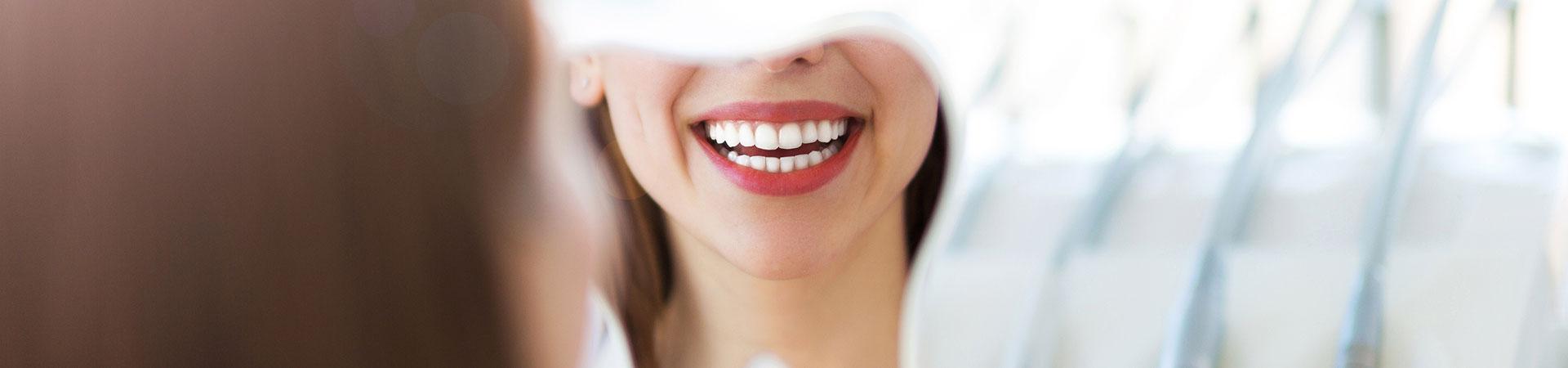 Woman looking at her beautiful teeth in a mirror. Oral hygiene Marietta, GA.