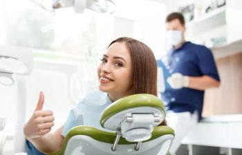 Happy young woman in a dentist chair showing her thumb up.
