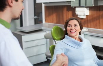 Happy mature woman in a dental chair shaking hands with a dentist.